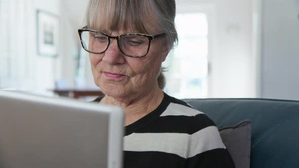 Thumbnail for Close up dolly shot of senior Caucasian woman using tablet computer at home