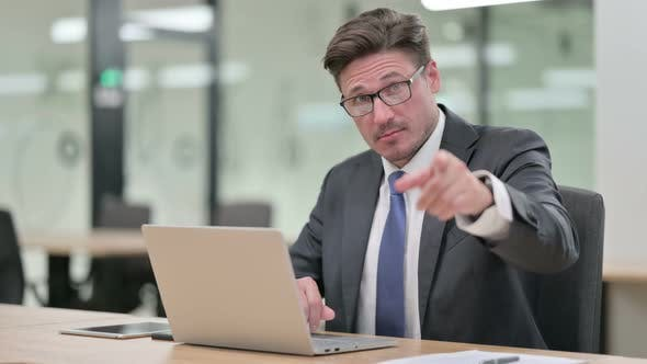 Thumbnail for Middle Aged Businessman with Laptop Pointing at the Camera