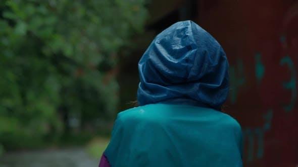 Teenager Walks in Rainy Weather Turning Back