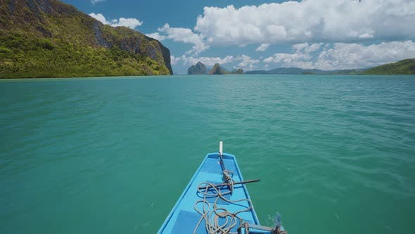 Island Hopping Tour Blue Boat Hover Over Open Blue Ocean Surface Between Exotic Karst Limestone