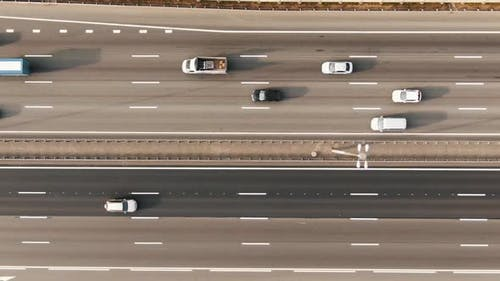 Autos and Trucks Drive Along Autobahn with White Markings