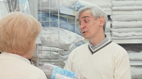 Thumbnail for Senior Man Choosing Bedding Goods with His Wife at Furnishings Store