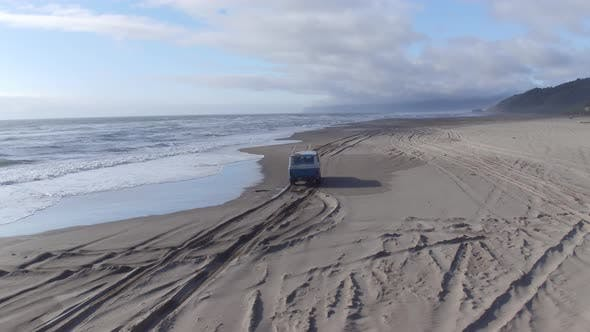 Aerial view of group of friends driving on beach in vintage vehicle