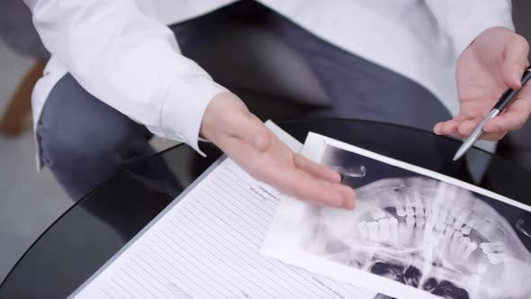 Dentist Discussing Jaw X-Ray with Patient