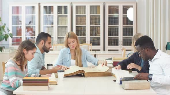 Cover Image for Group of Multiracial People Studying with Books in College Library