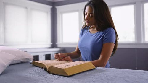 Young Latina woman studying religious text inside bedroom
