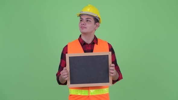 Thumbnail for Happy Young Multi Ethnic Man Construction Worker Thinking While Holding Blackboard