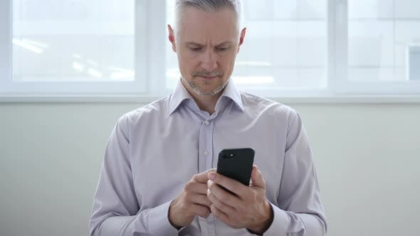Thumbnail for Middle Aged Man Browsing on Smartphone, Using Internet