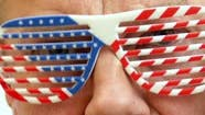 Serious Senior Mature Man Puts on Decorative Glasses in the Colors of the American Flag