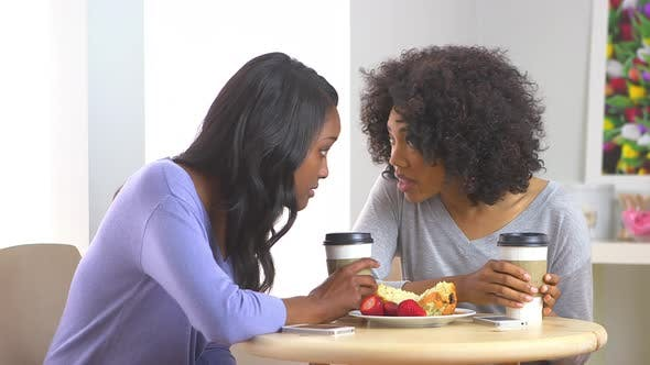 Thumbnail for African American friends having a whispered conversation at caf_