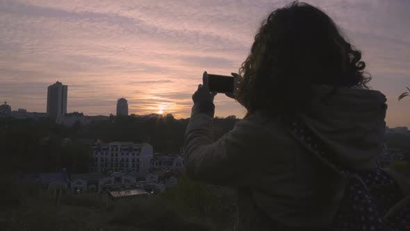 Inspired Female Student Filming Cityscape With Amazing Sunset on Smartphone
