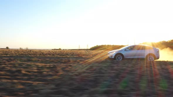 Thumbnail for Aerial Shot of Electrical Car Move on Off-road Route Leaving Dust Trail Behind. Modern Auto Driving