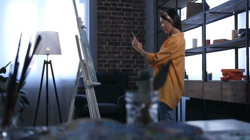 Smiling Female Painter Photographing New Artwork