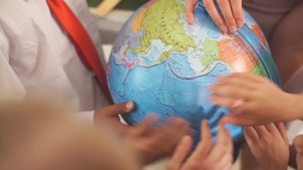 Thumbnail for Schoolchilds Looking at Globe with Teacher at Geography Lesson