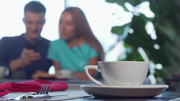 Thumbnail for Selective Focus on a Cup on the Table Couple Cuddling on the Background