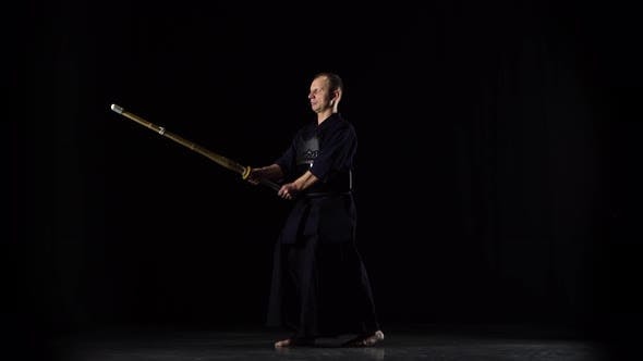 Thumbnail for Masculine Kendo Warrior Practicing Martial Art with the Bamboo Bokken on Black Background.
