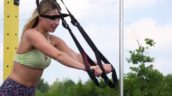 Thumbnail for A Fit Beautiful Woman Does Inclined Push-ups at an Outdoor Gym - Closeup