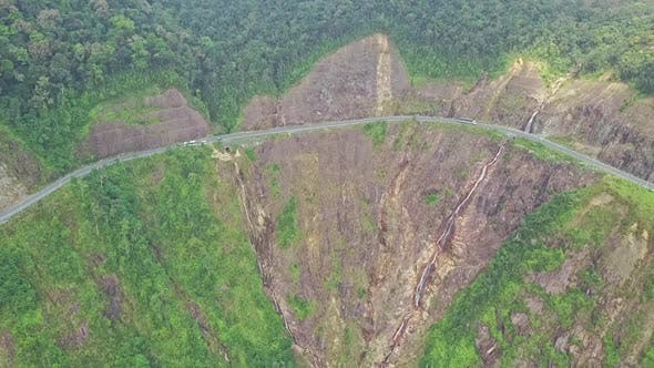 Drone Approaches Mountain Highway Curve on Steep Cliff