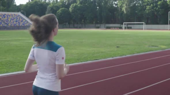 Athletic Young Girl Runs in the Stadium. Slow Motion