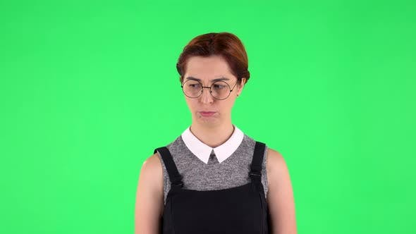 Thumbnail for Portrait of Funny Girl in Round Glasses Is Very Offended and Looking Away. Green Screen
