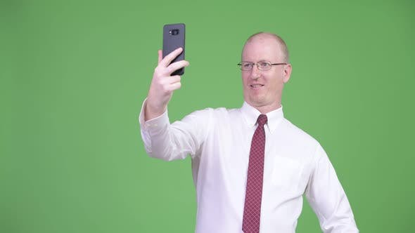 Thumbnail for Happy Mature Bald Businessman Taking Selfie