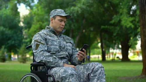Disabled Male in Uniform Scrolling Smartphone Application, Employment Service