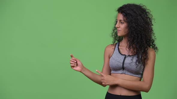 Thumbnail for Young Beautiful Hispanic Woman with Gym Clothes Showing Something