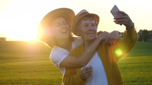 Thumbnail for Happy Elderly Grandmother Taking Selfie With Granddaughter At Sunset With Smartphone