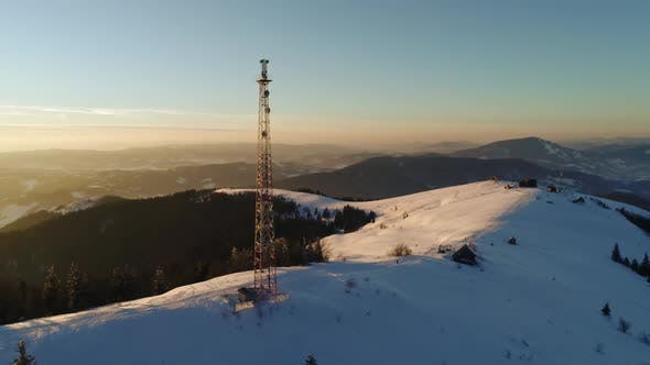 Flying Over Radio Tower in Mountains, Snow Covered Winter Landscape.