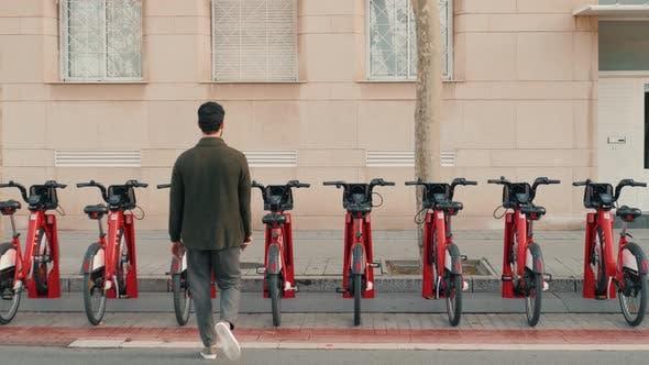 Tourist Man Take Electric Kick Scooter or Bike Bicycle in Sharing Parking Lot Tourist Phone