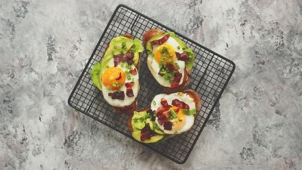 Köstliche leckere hausgemachte Toasts mit Spiegelei, Speck, Avocado, Salat und Schnittlauch