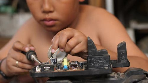Asian Boy Fixing Motherboard
