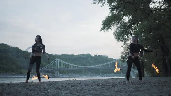 Thumbnail for Two Young Women Performing a Show with Flame Balls Standing on the Riverbank