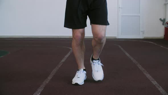Unrecognizable Runner Training Running Exercise on Treadmill in Gym Front View