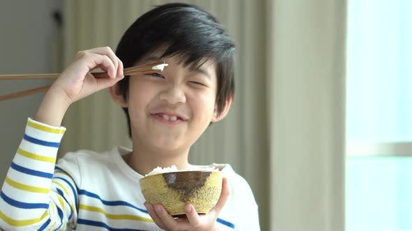 Cute Asian Boy Eating Rice With Chopsticks