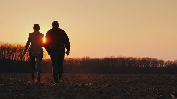 Thumbnail for Silhouettes of Two Farmers Walking Across the Field Towards the Rising Sun