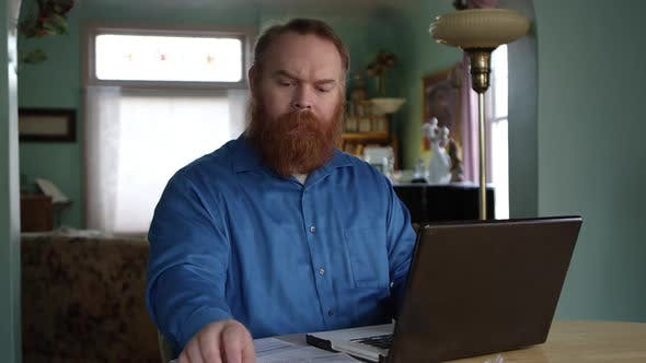 Thumbnail for Man paying bills online looking frustrated