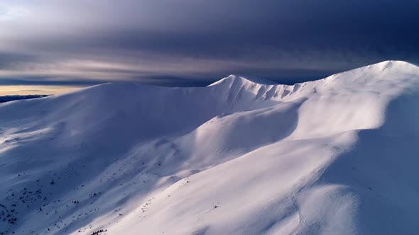 Flight over the turquoise snowy mountains illuminated by the day sun