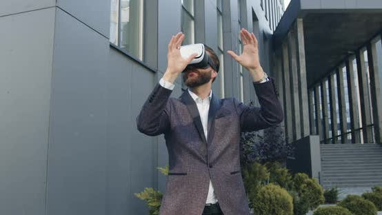 Thumbnail for Businessman in Augmented Reality Goggles Working Outdoors Near Modern Urban Building