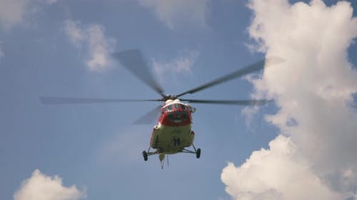 Emergency Service Helicopter Flying Against Clouds