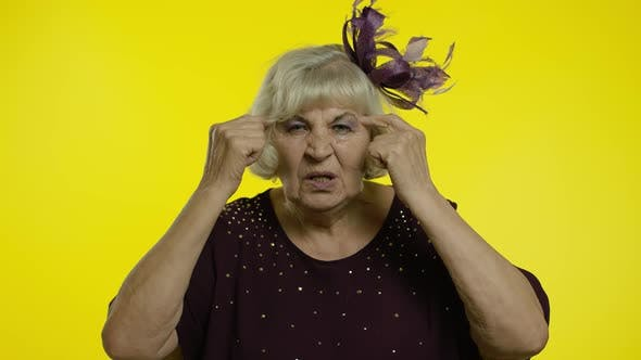 Thumbnail for Displeased Annoyed Senior Old Woman Showing Stupid Gesture. Elderly Grandma on Yellow Background