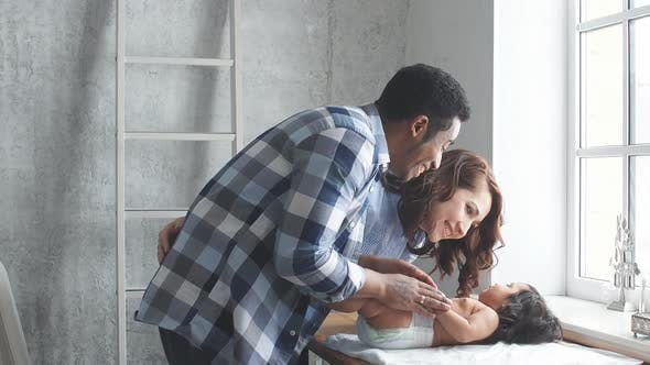 Cheerful Daddy and Mommy Massaging the Baby's Body