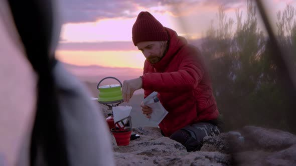 Man Makes Coffee When Camping at Sunset