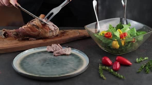 Woman cutting roasted turkey leg