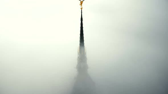Drone Ascending Above Thick Fog To Reveal Majestic Golden Angel Statue