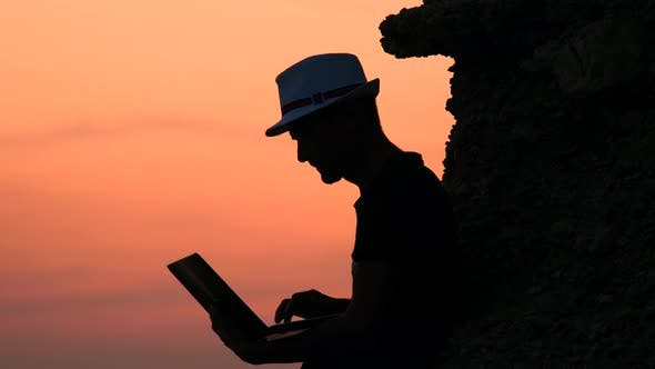 Cover Image for Preparing To Pitch. Male Freelancer Hipster with a Laptop Remote Work on the Beach on the Sunset