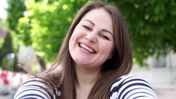 Thumbnail for Beautiful plus size girl looks at the camera and smiles