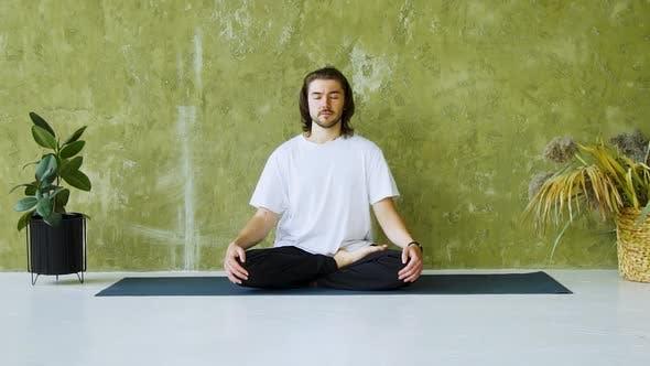 Calm Man Sitting on Yoga Mat in Lotus Pose