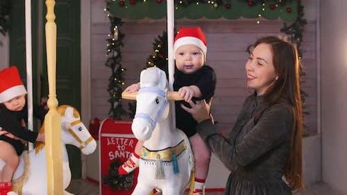 Babies Sitting on Christmas Carousel