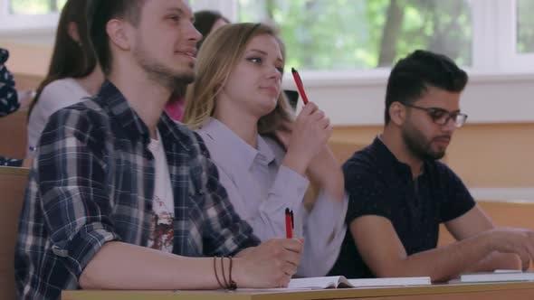 Groupmates Talking, Writing in Copybooks in University.